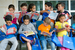 First graders engaged in Sifriyat Pijama books they recieved at school