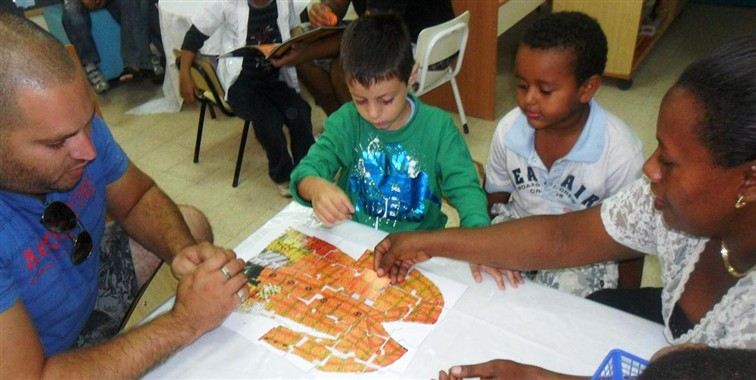 Children and their parents assemble a Joseph Had a Little Overcoat puzzle