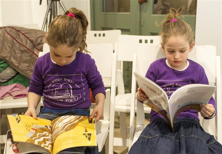 Two girls enjoying Sifriyat Pijama books at the national book fair in Jerusalem, Feb. 2015