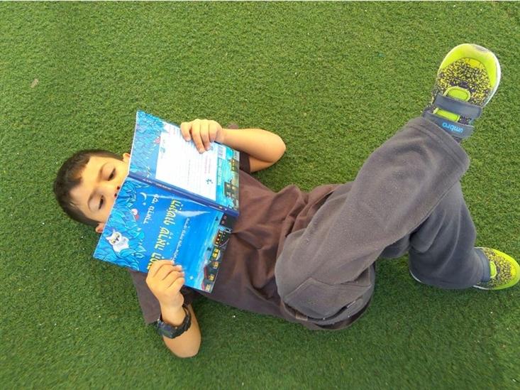 A boy enjoying his new book The Backward Owl, in Ramat Kramim school in Ashkelon